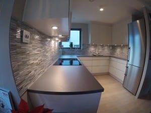Stavmosaikk i hvitt og grått er montert over kjøkkenbenk.